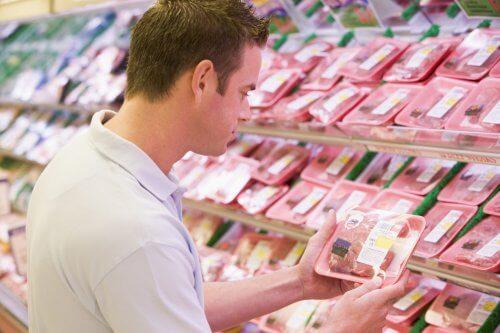 Man in supermarkt kijkt naar vlees