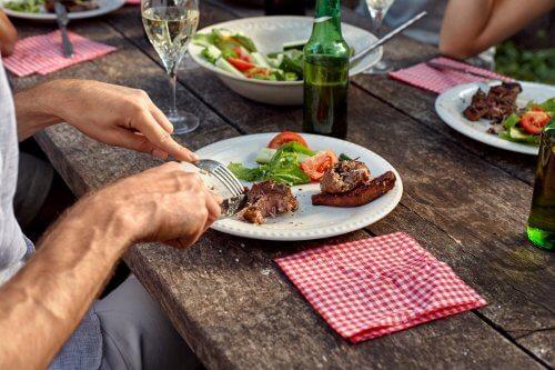 Man eet vlees op bord