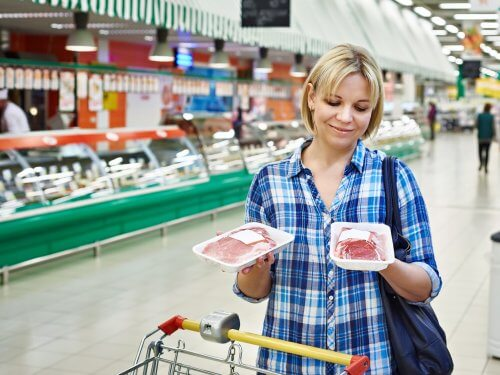 Vrouw checkt vlees in supermarkt