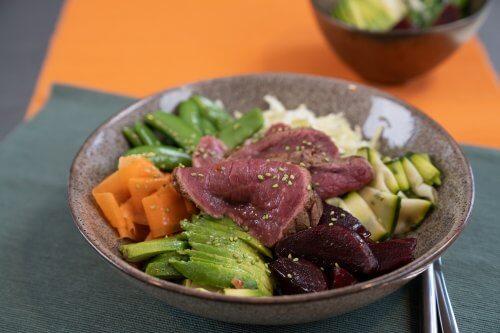 Poké bowl met gemarineerde runderlende en kleurrijke groente